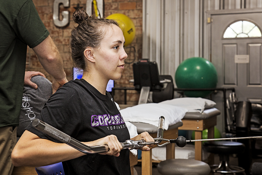 Patient exercising on cable rows