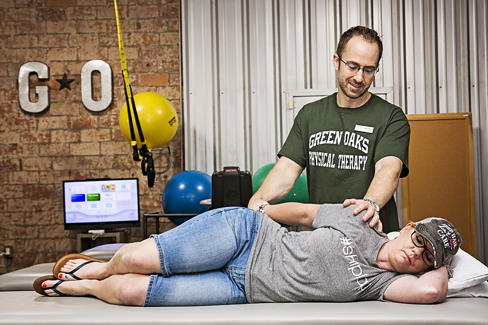 Therapist stretching on patient shoulder in side lying